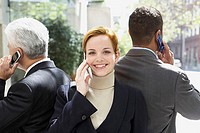 Portrait of a businesswoman with two businessmen talking on mobile phones