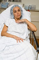 Portrait of a female patient lying in a hospital bed and looking serious