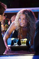Close-up of a female bartender looking at a young man and smiling