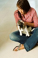 High angle view of a young woman sitting on the floor and holding her cat