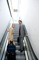 Businessmen travelling. Escalator.