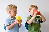 Two little drinking from a plastic cup