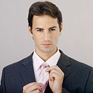 Portrait of a businessman straightening his tie