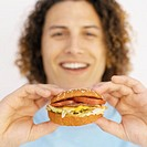 Portrait of a young man holding a burger