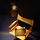 High angle view of a clapperboard on a director´s chair with a spotlight beside it