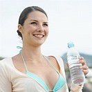 Low angle view of a confident woman at the beach holding a bottle of water