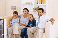 Portrait of a young couple watching television with their children (8-10)