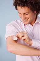 Close-up of a man applying a nicotine patch to his arm