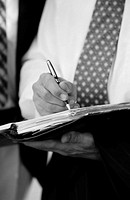 close-up of a businessman´s hands writing in a folder