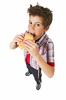Elevated view of a boy (12-13) eating a burger