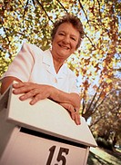 low angle view of an elderly woman leaning on a letterbox