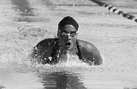 black and white shot of a young female swimmer swimming