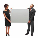 Portrait of businessman and businesswoman holding blank placard between them