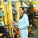 portrait of a young woman holding a hacksaw in a hardware store
