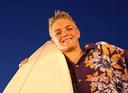 Low angle view of a young man standing with a surfboard