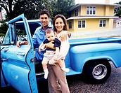 portrait of parents standing beside their car with their baby
