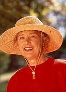 Portrait of an elderly woman wearing a straw hat