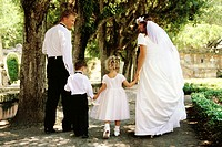 portrait of the bride and groom walking with two children