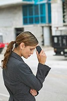 side view of a businesswoman holding her mobile phone to her forehead looking thoughtful