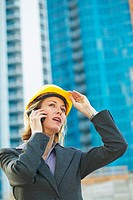 close up of businesswoman wearing a hard hat talking on a mobile phone