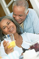 couple being affectionate while wife holding a glass of orange juice