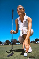 Low angle view of a young woman kneeling with a golf club