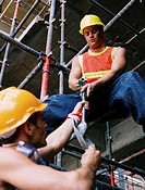 low angel view of construction workers tightening the metal scaffolding at a site