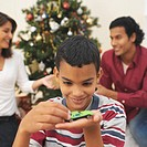 Boy (9-10) playing with a toy car with his parents in the background