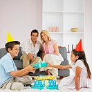 Boy(9-10) giving a girl( 7-8) birthday presents with parents in background
