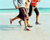 group of people jogging on the beach