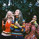 three young women blowing soap bubbles in a garden