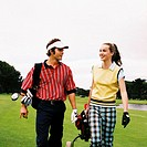 view of a couple at the golf course with their clubs