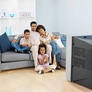 Front view of parents and two children watching television (9-11)