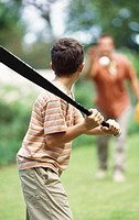 Father and son playing baseball in garden (10-11)