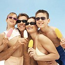 Portrait of a family at the beach eating popsicles