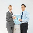 Front view of two business executives standing beside water cooler drinking cup of water