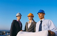 Front view portrait of three business executives holding blueprint and wearing hard hats