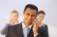 Portrait of a young businessman talking on a mobile phone smiling with a group of business executives standing behind him