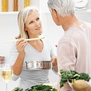 Close-up of mature woman feeding mature man spoon of sauce from saucepan with young man cutting cabbage