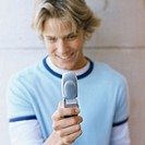 Front view of young man holding mobile phone