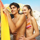 Close-up side view of young couple standing at beach and holding surfboard