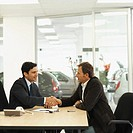 Side view of salesman and customer shaking hands in office