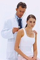 Portrait of a male doctor examining a young woman´s back with a stethoscope