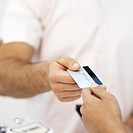 Close-up mid section of patient paying dental nurse with credit card