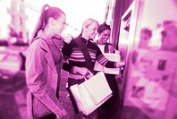 portrait of young women at an automatic cash machine