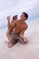 low angle view of a young couple playing on the beach