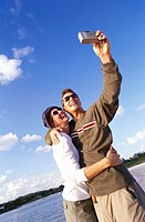 low angle view of a young couple taking a photograph of themselves at the beach