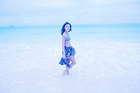 tungsten shot of a young woman wading at the beach