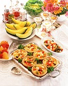 high angle view of a platter of fruit tarts served on a silver tray kept beside wine and condiments