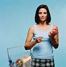 view of a young woman standing with goods in a shopping basket